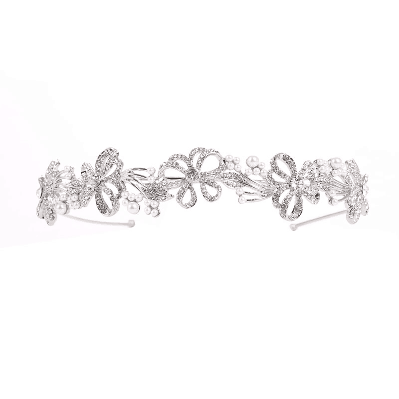 The Abby headband is a stunning statement headband perfect for weddings, engagements, or a day at the races. The beautiful design is embellished with clear crystals and simulated ivory pearls on a silver finish.
