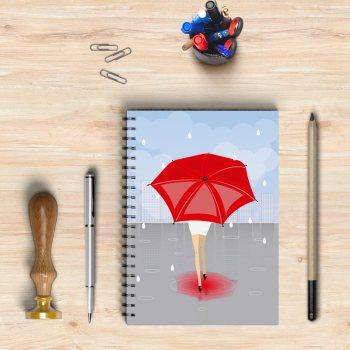 Libreta con un diseño de una mujer con paraguas rojo bajo la lluvia