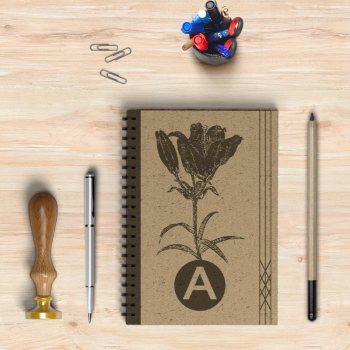 Libreta con un dibujo de una flor en negro y la letra A
