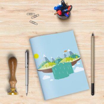 Libreta con el dibujo de unas montañas sobre una isla flotante