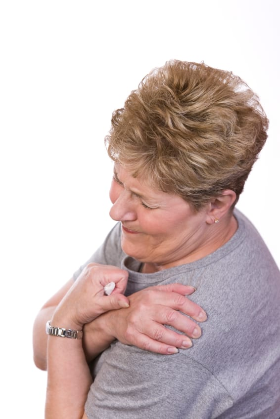 photo of woman holding shoulder in pain