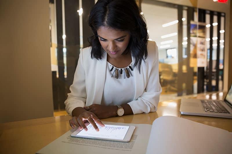 woman using digital tablet sitting at desk