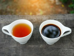 White cup of earl grey tea and coffee on wooden background