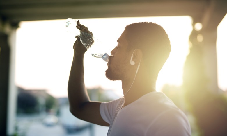 Attractive athlete sportsman drinking water after training and h