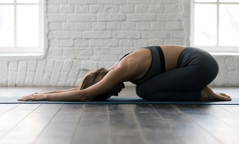 Young woman practicing yoga, lying in Child pose, Balasana exercise