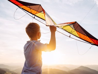 Boy prepare to fly a kite over the mountain hills