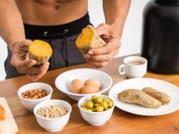 cropped image of muscular man without clothes hold sweet potatoes showing healthy food menu on the table
