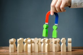 Businessman with a magnet pulls green figures of people out of the crowd. Recruiting new workers. Search for right people and talented workers with great career potential. Formation of a new team
