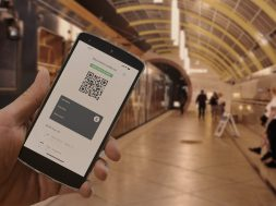 The digital green pass of the european union with the QR code on the screen of a mobile held by a hand with blurred train station in the background. Immunity from Covid-19. Travel without restrictions