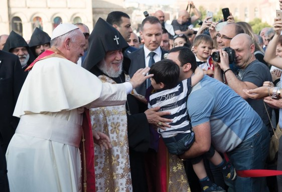 Pope Francis and Catholicos Karekin II, right, reach out to touch a child during an Ecumenical encounter and prayer for Peace in Yerevan's Republic Square, Armenia, Saturday, June 25, 2016. Pope Francis is on a three-day trip to Armenia. (L'Osservatore Romano/Pool photo via AP)