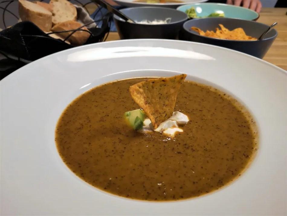 Ein Teller Bohnensuppe mit Nacho, Avocado und Sauerrahm