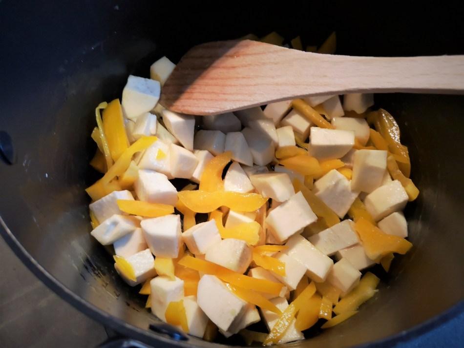 Maniok Stückchen und die Paprikastreifen werden im Topf angeröstet.