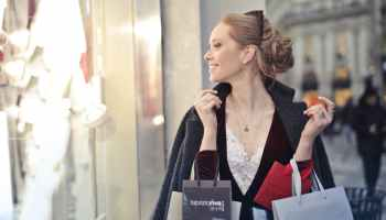 Smiling woman in blonde hair, white blouse and black coat holding shopping bags as she walks past a designer store.