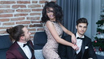 Woman dressed in a beige Christmas party dress with two men dressed in suits at a holiday party.