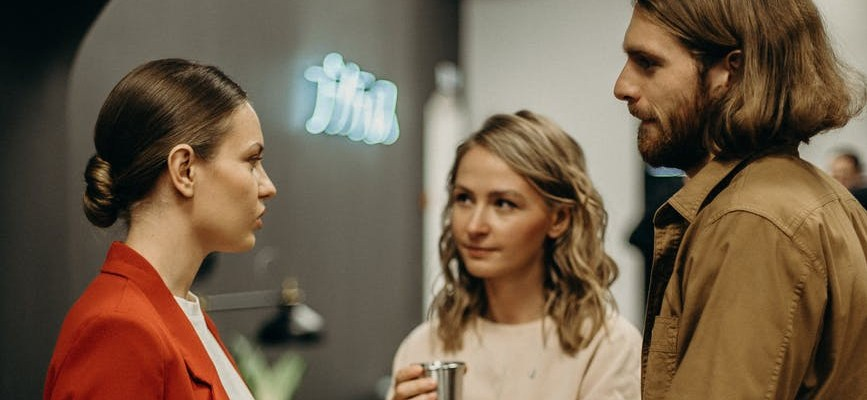 Two women and a man talking in the workplace and showing interest in one another.