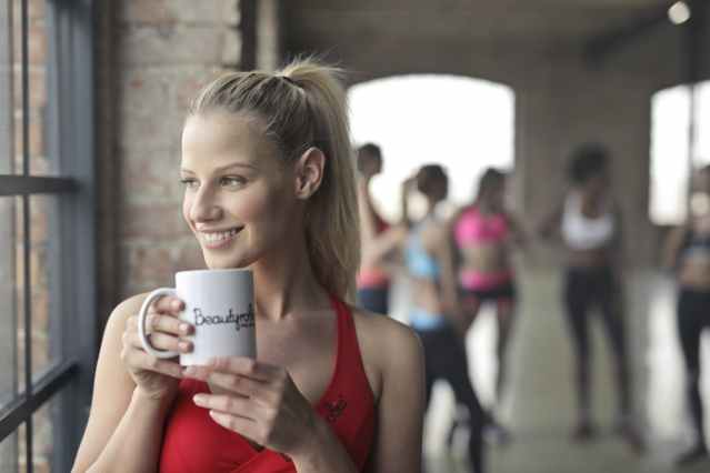 Blond girl in a red top looking out of a gym window and drinking from a white coffee cup.