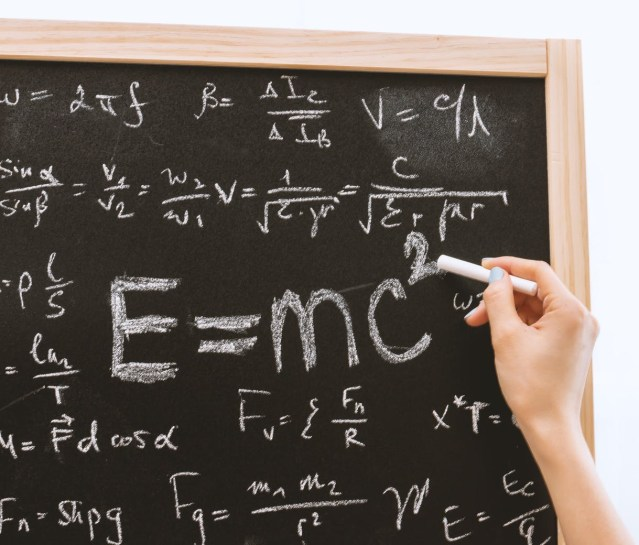 Person holding a chalk and writing equations on a blackboard to demonstrate that business writing skills can be improved with simplicity.