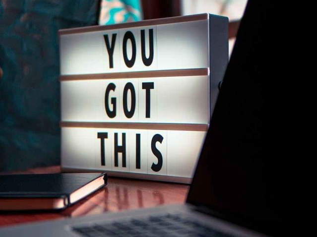 """A lighted sign that says, """"you got this"""" on a desk with a book and laptop in the foreground."""