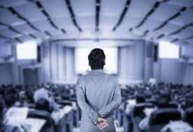 Man dressed in a grey suit looking down an auditorium filled with an audience listening to a speech.