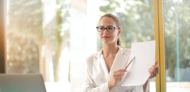 Woman dressed in a white blouse sitting at a desk and pointing to a white paper with a pen.