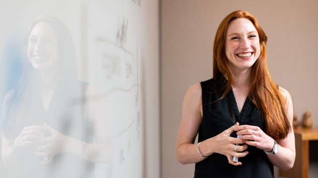 Woman smiling while speaking and confidently making a presentation at work.