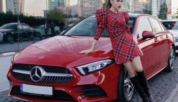 Woman in a red dress and black boots leaning on a shiny red Mercedes Benz car.