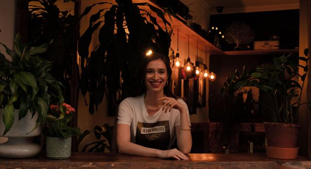 Girl in black hair wearing a white and black t-shirt smiling and standing behind a wood counter.