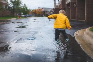 child jumping into puddle