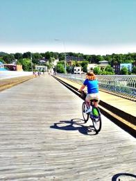 Becky riding her bike share bike across the ped bridge