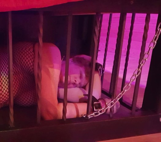 Me lying chained in a cage under the bed st the Stoxx dungeon.