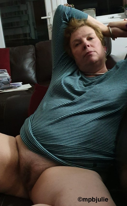 I'm wearing a blue stripy top, my arms behind my head. I am relaxing on the sofa without underwear. Relaxed and ready.