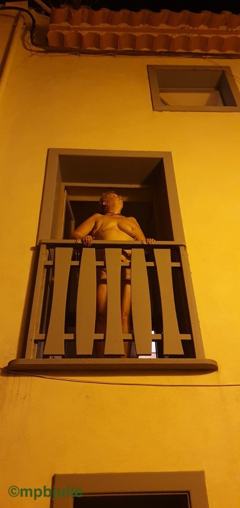 I am standing at the tall open window naked. It is night time. In front of me is a wooden railing.