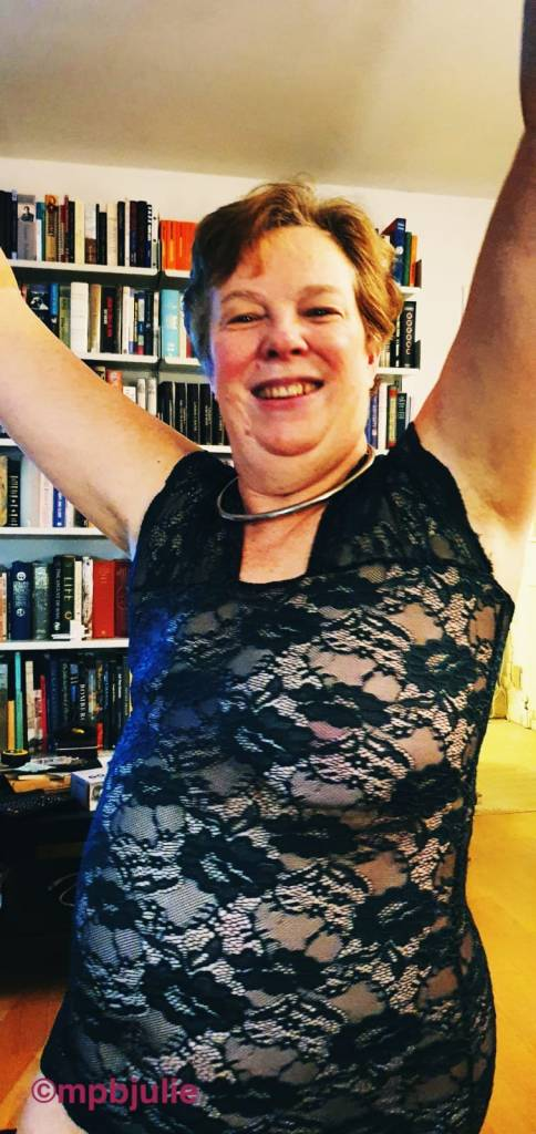 Me wearing a lacy, see through dress with arms raised in celebration.