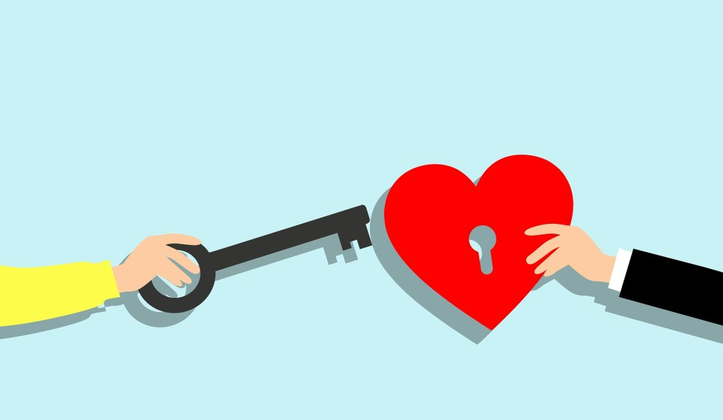 A hand holdig a key and another holding a redd heart