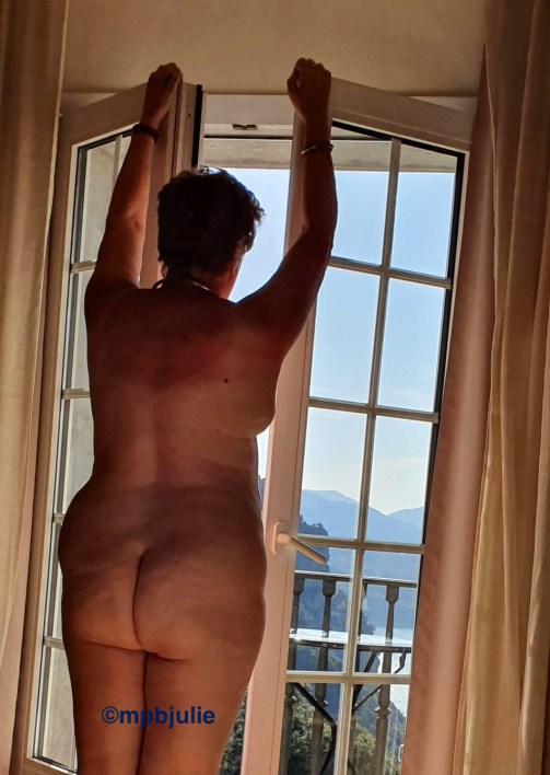 I'm standing facing the window and the photographer is behind me. I'm naked and outside there is a balcony, lake and mountains