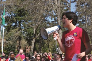 Junior Lillian Ferraz leads a call-and-response chant to a crowd of approximately 50 students and faculty members during the International Workers Day protest in Red Square on May 1.  Her pin has the name of the union PLU contingent faculty members are trying to join.