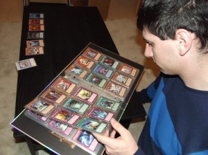 "Yu-Gi-Oh! Club president Andrew Morris flips through his binder of cards. ""It's important to keep the cards in good condition to protect their value,"" he said."