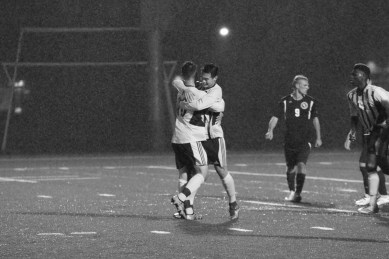 PHOTO BY BAILEY PLUMB: Sophomore Eddie Na (9) hugs senior Troy-Mikal Oliger (10) after scoring a penalty kick. Na was second in the league with 12 goals.
