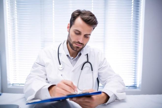 male-doctor-writing-on-clipboard-HWR2NTV