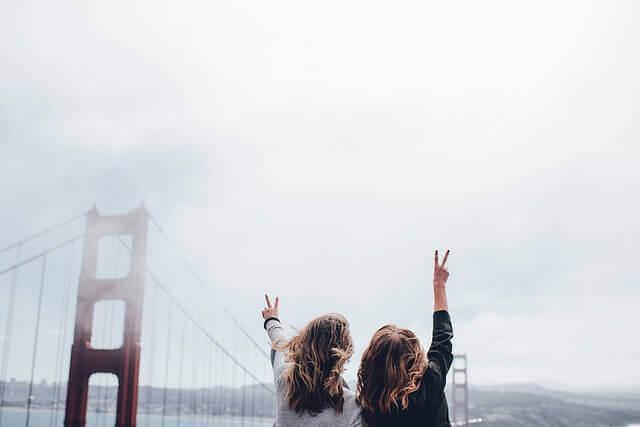 大きな橋と空に向かってピースサインを出す2人の女の子