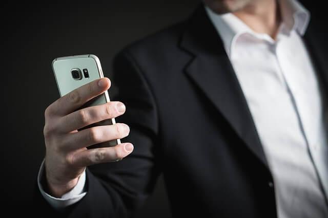 片手に持ったスマートフォンを凝視するスーツ姿の男性