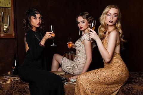 派手なパーティードレスに身を包みグラスを片手にソファに座る女の子たち