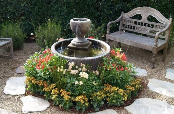 Simple-front-yard-fountain-with-wood-chair-and-beautiful-flowers