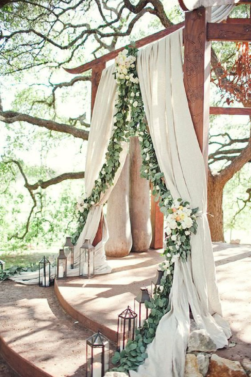 Decorated wood arch with long veils and floral composition