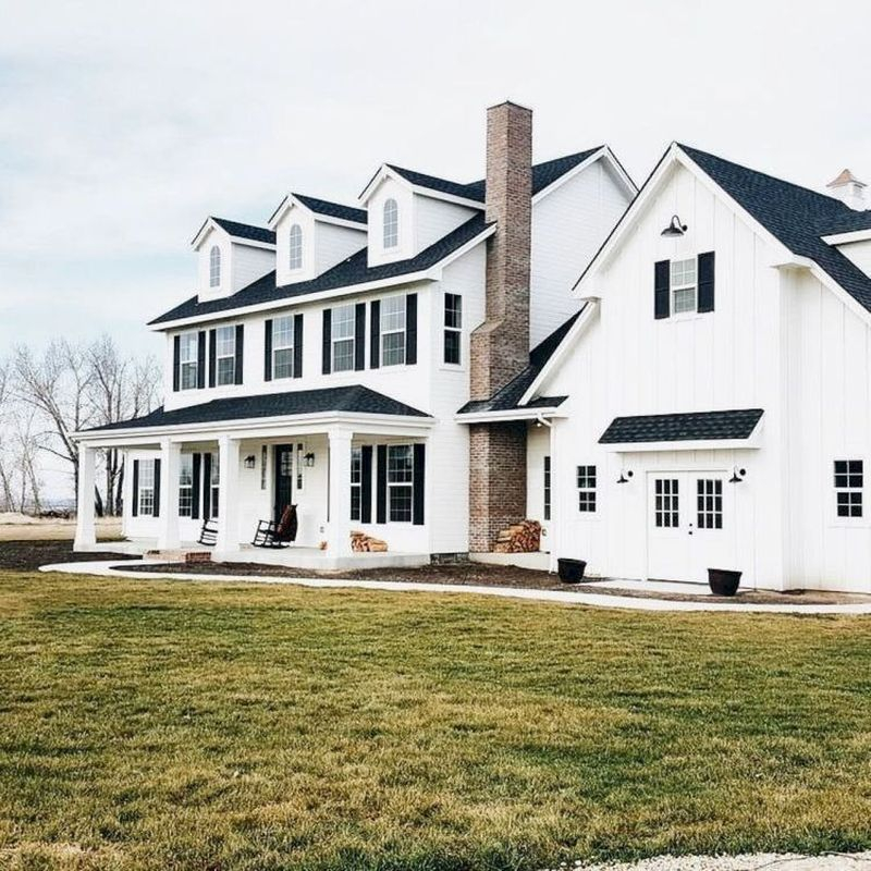 Modern farmhouse exterior design with dark room, white walls, plank siding, white windows & trim, black shutters, brown stone, chimney, covered front porch