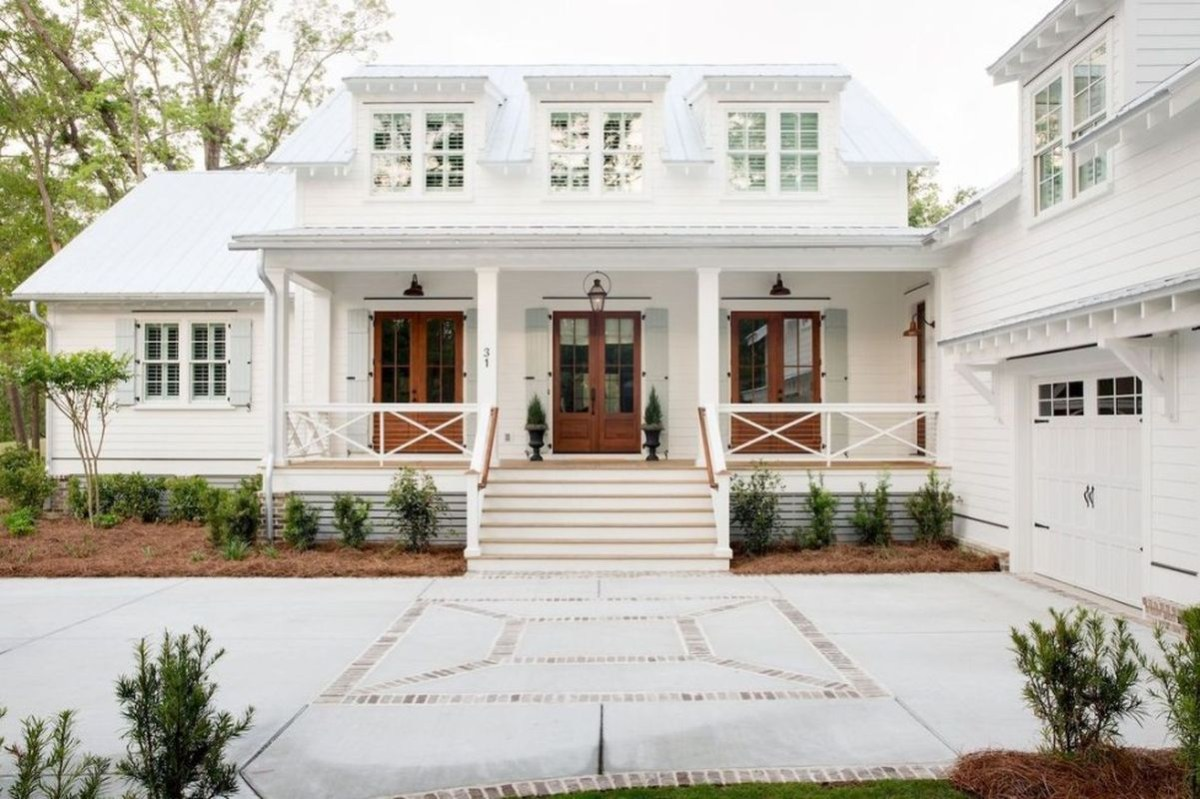 Modern farmhouse exterior with side garage, white walls, light grey tin roof, covered porch, rich brown wood doors