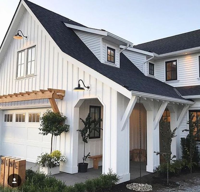 New construction modern farmhouse for exterior design with white plank siding, dark roof, covered porch with columns, extra overhang & angled beams, natural wood trellis above garage door