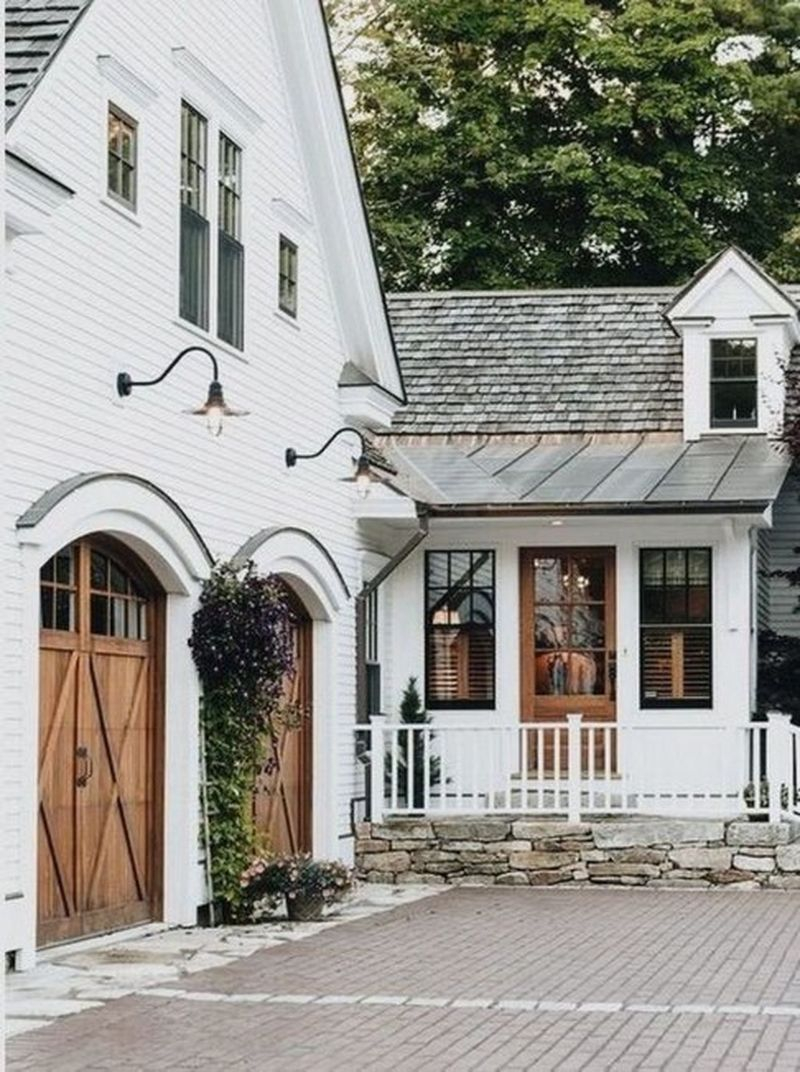 Old charm modern farmhouse combine with white exterior, black windows, natural wood doors, stacked ledge stone & cobblestone, shake shingle and tin roof combo