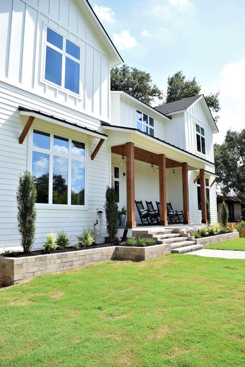 Stunning creekside designs modern farmhouse with white exterior, dark shingle roof, natural wood beams & awning anchors, covered porch with wood ceiling