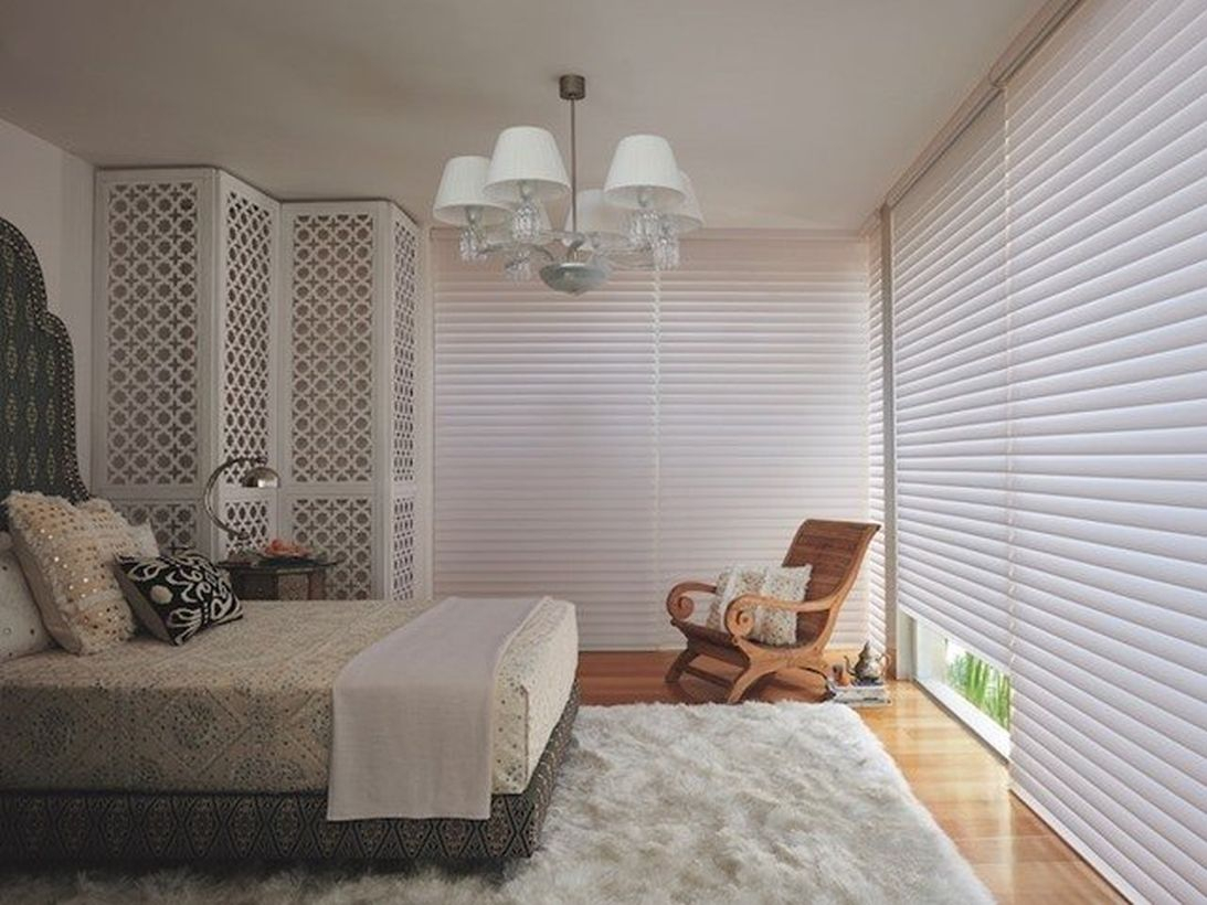 Stunning white bedrooms with white walls, white rectangular carpets, white blankets, large white curtains, wooden floors and chairs to create calm
